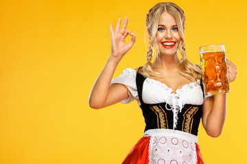 Young sexy Oktoberfest girl waitress, wearing a traditional Bavarian or german dirndl, serving big beer mugs with drink isolated on yellow background. Woman showing ok sign with fingers.