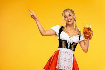 Young sexy Oktoberfest girl waitress, wearing a traditional Bavarian or german dirndl, serving big beer mugs with drink isolated on yellow background. Woman pointing to looking left. Wall mural