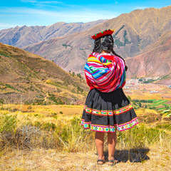 Square format of an indigenous Quechua lady with traditional hair style, dress and hat looking over the Andes mountain range in the Inca ruin of Tipon near Cusco, Peru.
