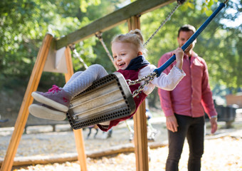A small toddler girl with a father on a swing on a playground.