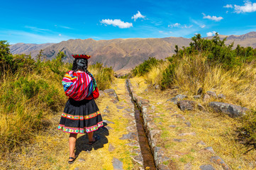 Young quechua indigenous woman walking along an inca aqueduct in the archaeological site of Tipon near the city of Cusco, Sacred Valley of the Inca, Peru.