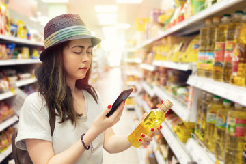 A young beautiful woman holds a bottle of oil in her hand and takes a picture of her on a mobile phone. In the background shelves with products. The concept of modern shopping in the store. Light
