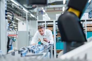 Businessman in a modern factory hall examining workpieces
