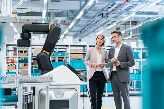 Businessman and businesswoman in a modern factory hall looking at robot