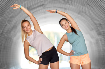 fitness, sport and healthy lifestyle concept - smiling young women or female friends with activity trackers stretching outdoors