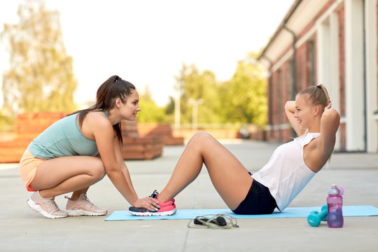 fitness, sport and healthy lifestyle concept - young woman assisting her friend doing sit-ups on mat outdoors
