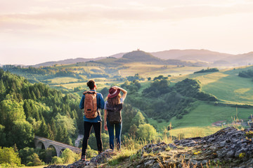 Fototapeta Rear view of young tourist couple travellers hiking in nature, resting. obraz