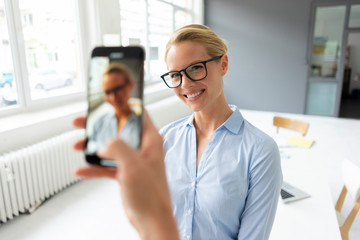 Smartphone picture of young businesswoman in office