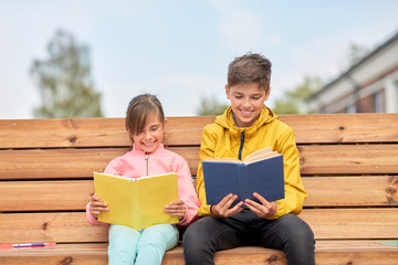 education, childhood and people concept - happy school children or brother and sister reading books sitting on wooden street bench outdoors