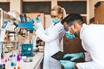 Two middle age scientists and researchers work in chemical laboratory.