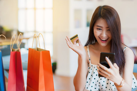 Asian girl shopping online happily.A multicolored paper bag placed next to it.