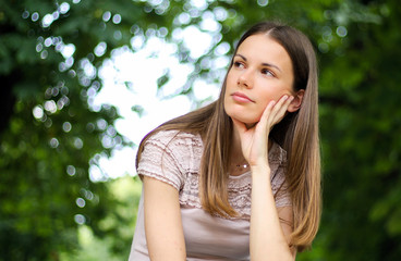 portrait of a pretty thoughtful lady sitting on a banch in a park
