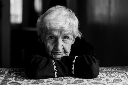 Portrait of old lady in a dark key. Black and white photo.