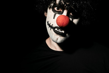 Close up portrait of a scary clown in a black wig and makeup. A man in a costume of a creepy clown with a red nose.