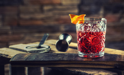 Cocktail Negroni on a old  wooden board. Drink with gin, campari martini rosso and orange