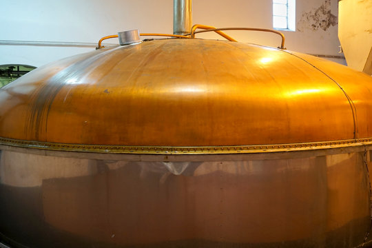a large copper mash tun in a whisky distillery