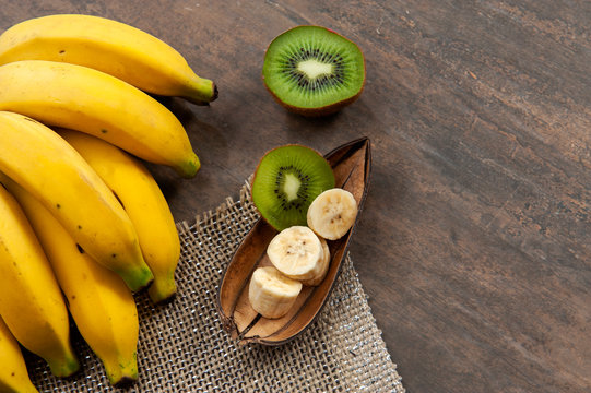 Fruit, banana peel, Kiwi fruit.Half kiwi and chopped bananas.Vitamin C, potassium.Again wood color background.Top view.Top space. Text space.