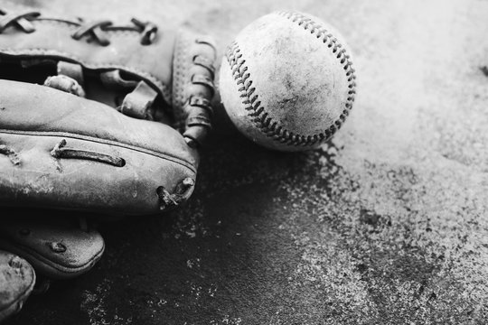 Ball with baseball glove close up shows old leather mitt used for the sport in black and white.