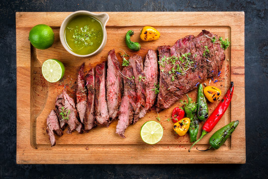 Modern design barbecue dry aged wagyu bavette de flanchet steak with chili and chimichurri sauce as top view on a wooden cutting board