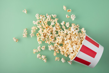 Overturned striped paper cup with delicious fresh popcorn on green background. The concept of entertainment.