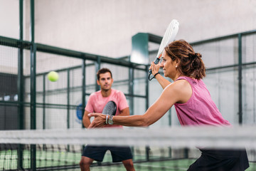 mixed padel match in a padel court indoor