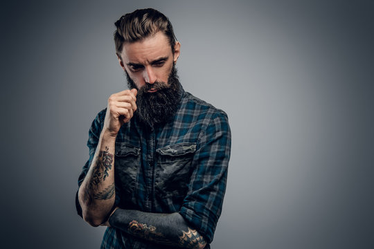 Bearded skinny man with tattooes feels dispair and sorrow while thinking about life.