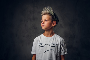 Pensive little kid is standing at dark photo studio while posing for photographer.