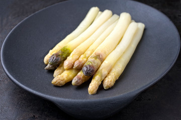 Traditional blanched white asparagus with purple heads as top view on a cast iron design plate with copy space