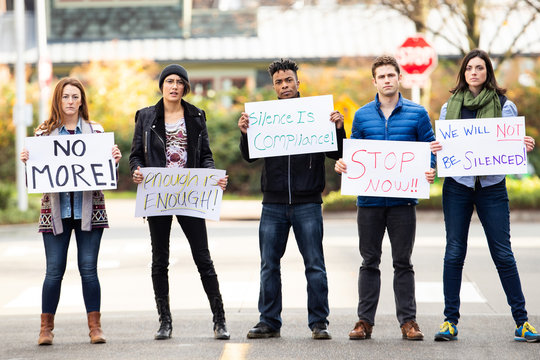 Group of five people protesting outside with signs