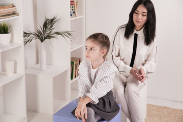 Female psychologist counseling little girl in the cabinet