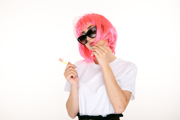 Young pretty girl with pink hair and sweet lollipop isolated in a white studio