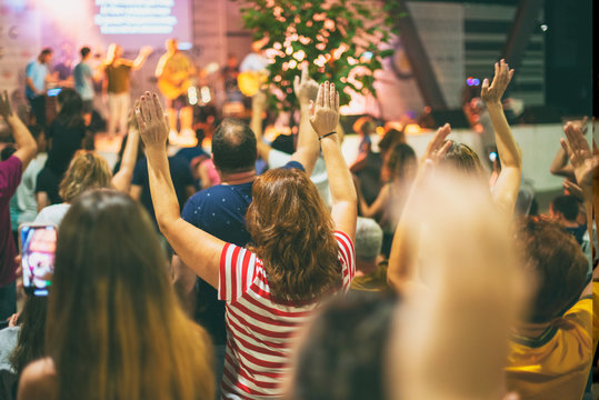 People worshiping God, with hands up.