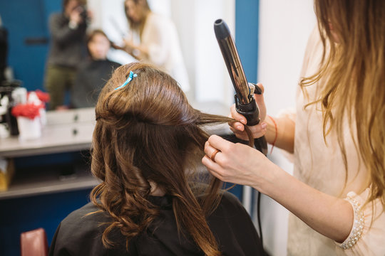 beauty, hairstyle concept, happy young woman and hairdresser with hair iron making hairdo at hair salon. Woman Having Hair Stylized Hairdresser. Smoothes Hair Curling. Stylist Using Tool for Modeling