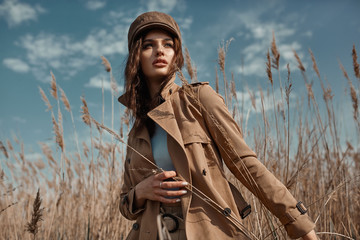 Beautiful Young Stylish Girl in Trench Coat Walking Autumn or Spring street. Autumn outdoor fashion. Wall mural
