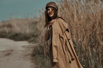 Beautiful Young Stylish Girl in Trench Coat Walking Autumn or Spring street. Autumn outdoor fashion.
