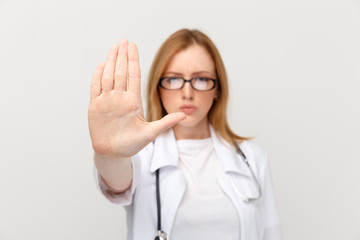 Sserious woman doctor in glasses showing stop sign isolated in the white studio