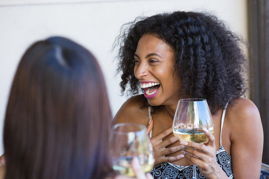 young woman laughing and drinking wine