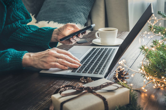 Christmas sales. Woman shopping with smartphone by laptop in home interior. Xmas. Planning holidays.