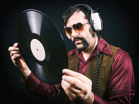Man wearing authentic vintage 1970's era clothing, including a vest, sunglasses and long collared shirt. Holding an analog classic vinyl record and wearing headphones.