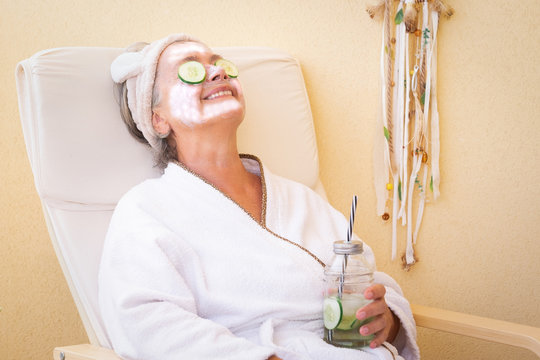 An elderly woman takes care of her face with a special cucumber-based cleaning mask. Sitting and relaxing outdoors on the terrace with a healthy drink. Bright light
