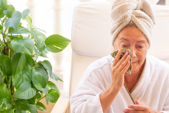 A senior woman sitting  on the terrace taking care of their wellness. White bathrobe and towel on the hair. Removing the beauty mask from her face. Peaceful and relaxing moments. Bright light