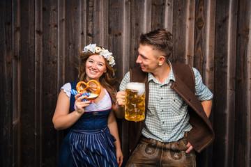 Junge Frau und mann mit Bierkrug und Brezel auf einem Holzhintergrund .Oktoberfest-Konzept
