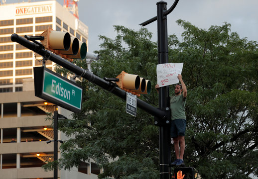 A man who climbed a traffic light holds a sign protesting against lead in drinking water outside the venue of the 2019 MTV Video Music Awards at the Prudential Center, Newark