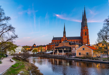 Wall Murals Old building Sunset view of Uppsala cathedral reflecting on river Fyris in Sweden