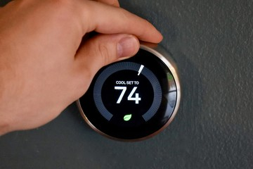 Hand adjusting temperature on electric thermostat