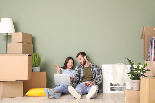 Young couple with cardboard boxes and laptop after moving into new house