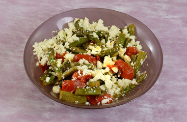 Asparagus and tomato side dish with crumbled feta cheese topping