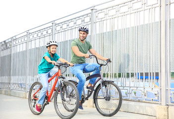 Happy father and son riding bicycles outdoors Fototapete