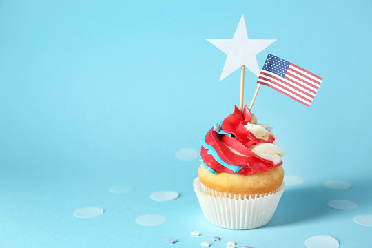 Tasty patriotic cupcake on color background