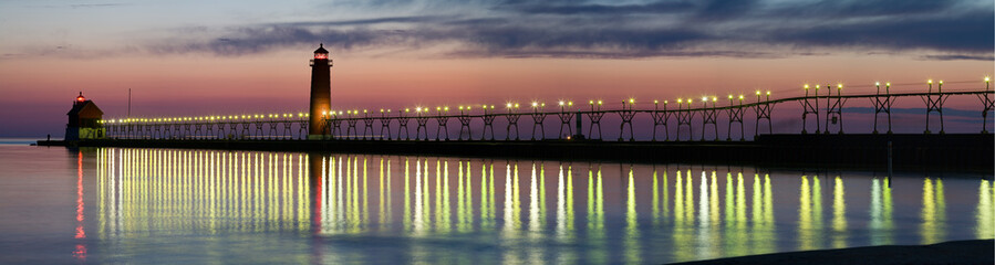 Foto auf Acrylglas Lachs Panorama of Grand Haven Lighthouse at sunset with catwalk lights reflected in Lake Michigan